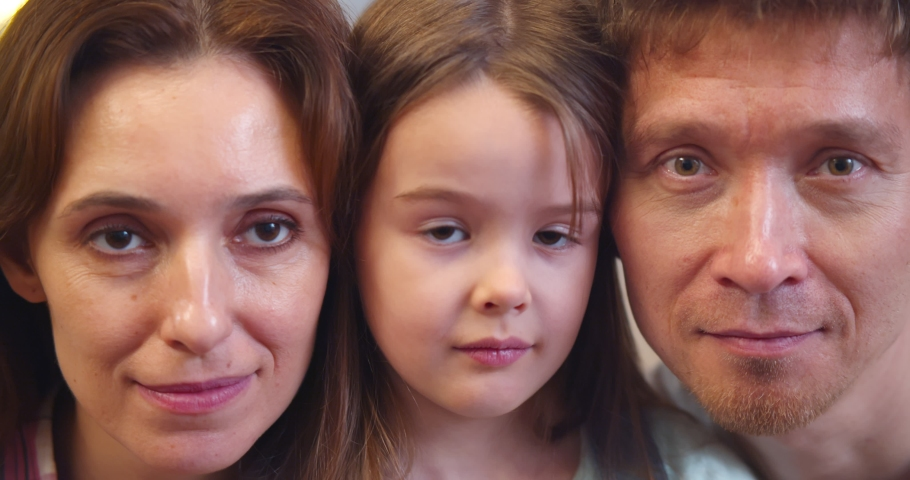 Close up portrait of happy smiling mother, father and little daughter. Headshot of loving young parents and preteen girl child looking at camera posing together | Shutterstock HD Video #1067697536