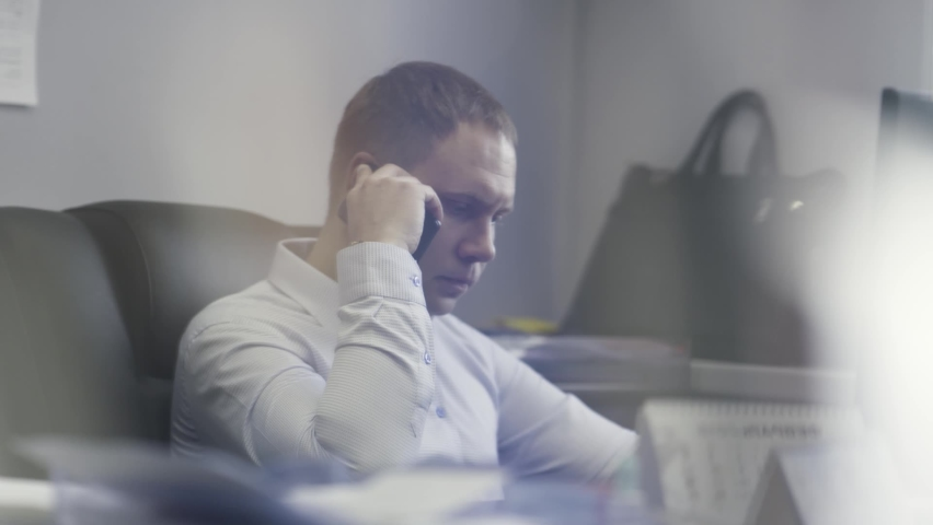 Businessman working in his office in front of computer screen. Action. Side view of male in a shirt talking on his mobile phone about work. | Shutterstock HD Video #1067699363