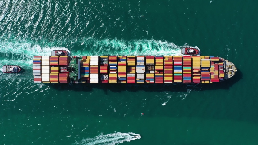 Large Container Ship in Sea. Aerial Top-Down View. Drone Flies Sideways.