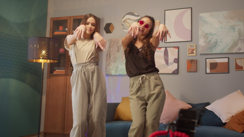 Teenagers womans shooting together dancing at home when making video for social media, stories hip hop popular trandy dance, students at home make content Royalty-Free Stock Footage #1067757863