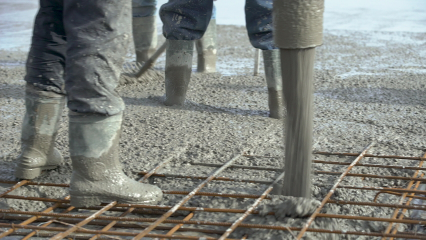 Concreting of reinforced concrete slab. Worker concretes foundation, rebar, pour cement mortar on reinforcing mesh or cage from pump concrete mixer. Builders are building a factory, hangar, house Royalty-Free Stock Footage #1067765384