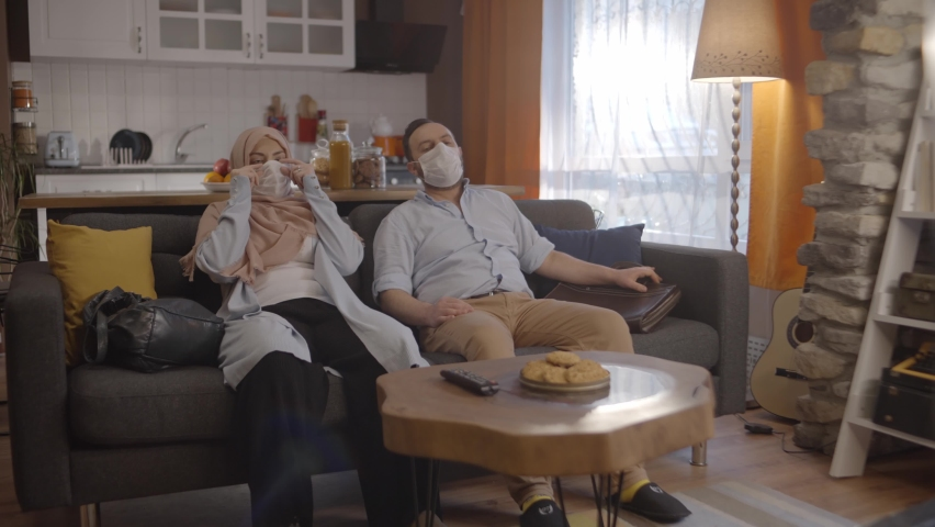 The young woman in hijab and the young man with a beard, who comes home tired from outside, leave themselves on the sofa and take off their masks.  | Shutterstock HD Video #1067770307