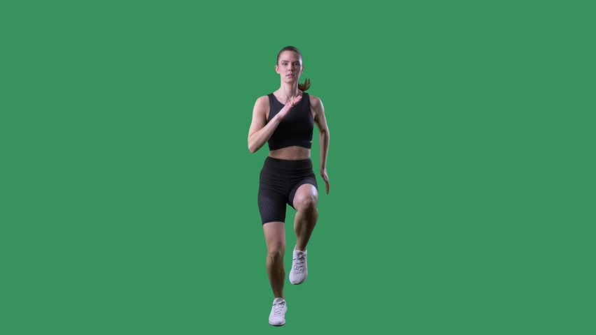 Slow motion of fit woman doing high knee exercise front view. Full body on chroma key green screen.