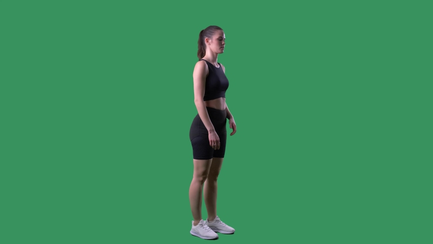 Slow motion side view of athletic woman runner doing high knees exercise. Full body on chroma key green screen.