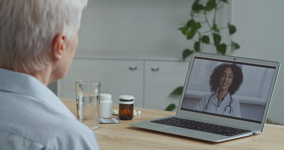 View from behind aging sick woman patient grandmother makes video call on laptop to doctor speaks to webcam talk with therapist woman specialist online conference, remote consultation during lockdown Royalty-Free Stock Footage #1067776853