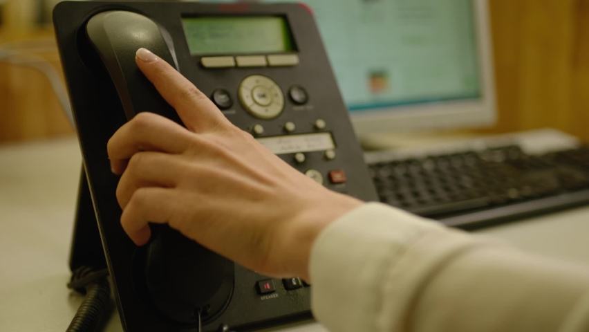 Close-up hand of woman pushing  the  button of the  black landline phone and answers. Call center. Operator picking up the phone for answering  the questions. Office room. Customer support center.