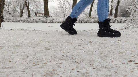 Girl walking on snow in black boots in the winter afternoon, with copy space.