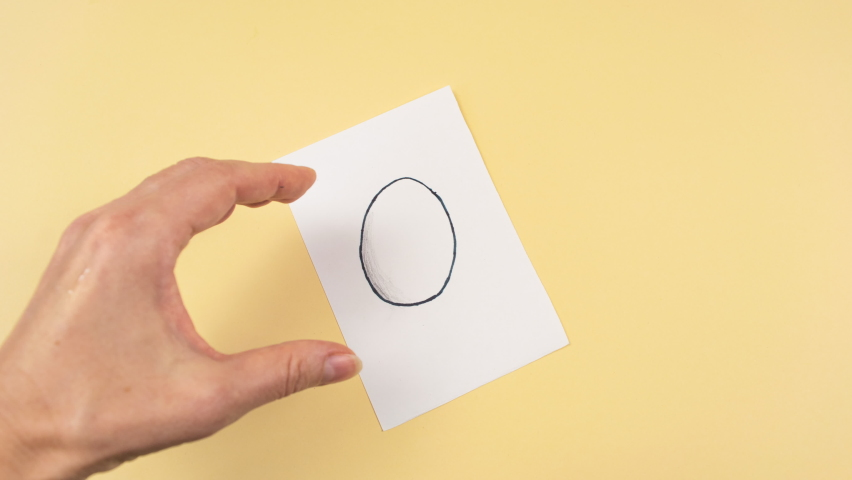 4k Drawing of an egg appears on a white piece of paper. Then the Woman's hand takes out real chicken egg from drawn one. Yellow background. Easter creative concept. Copy space. Stop motion animation.