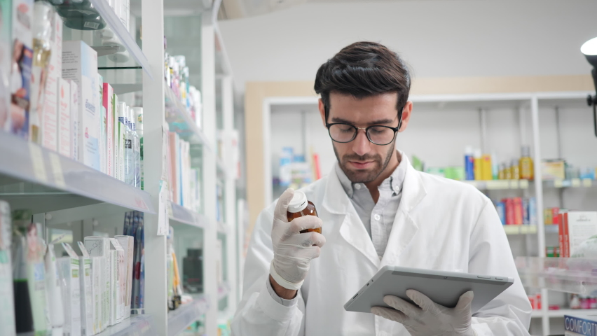 Male pharmacist using digital tablet and wear gloves reduce exposure checking stock inventory in modern pharmacy. Prevention of infectious diseases, touch, New Normal Concept  Royalty-Free Stock Footage #1067833298