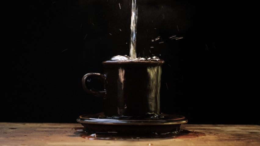 Steaming hot water poured into a stoneware cup until it overflows onto the saucer and table. Slow motion 4k.  Royalty-Free Stock Footage #1067879813