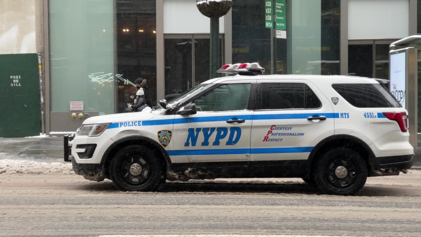 NYC, USA - FEB 18, 2021: NYPD police vehicle driving away in snow on winter day Midtown Manhattan New York City.