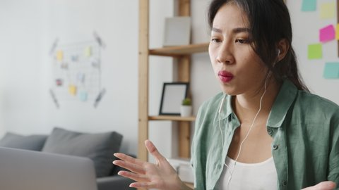Asia businesswoman using laptop talk to colleagues about plan in video call while smart working from home at living room. Self-isolation, social distancing, quarantine for corona virus prevention.