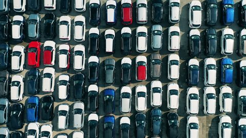 Car dealer parking lot full of new automobiles. Top view of motor park full of brand new cars