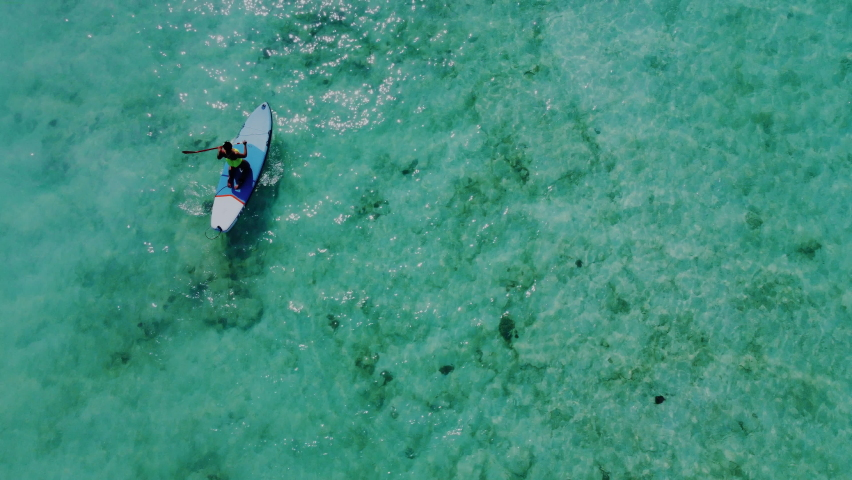 Aerial Top View of Sporty Young Woman while She Riding on Sup Board in Turquoise Water. Inflatable Sup Board or Surfboard, Paddle Board Girl on Water Surface, Drone Shoot. Royalty-Free Stock Footage #1067920151