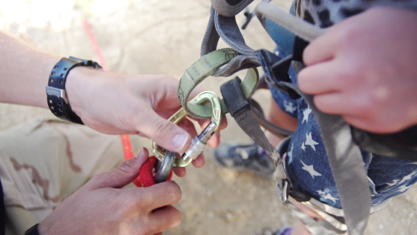 Instructor securing a climber with rope and carbine. Preparation before climbing. Slow-motion. | Shutterstock HD Video #1067934833