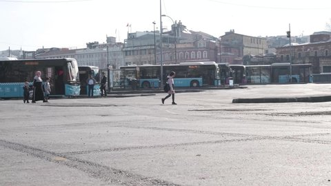 Eminonu, Istanbul, Turkey - 02.18.2021: municipal buses parked in bus depot and waiting for departure time to move and people walking around 4K high resolution