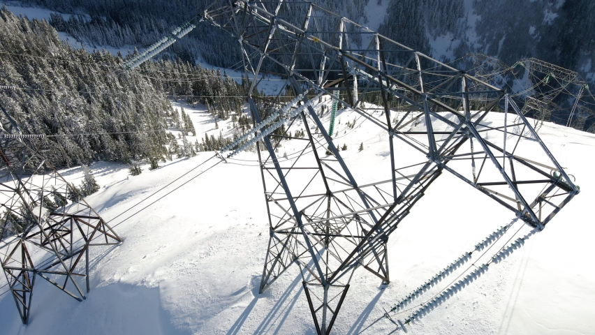 Electrical Grid Powder Lines Transfer Energy in Snowy Mountains Aerial View, Aerial view of utility towers in the backcountry wilderness of Washington State