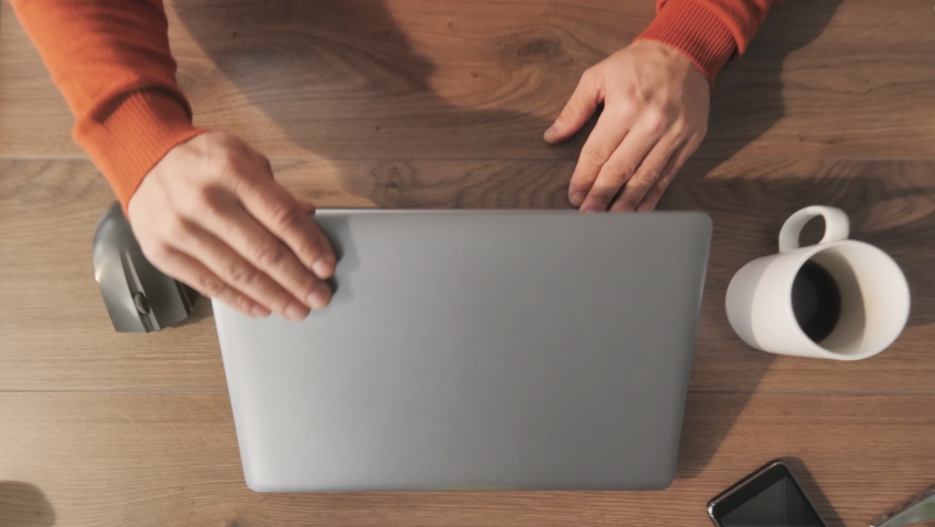 man working from home at her desk opens laptop computer top view overhead shot,zoom out of businessman opening notebook and start typing writes email surfs the internet drinks coffee Royalty-Free Stock Footage #1068013637
