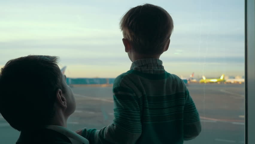 Slow motion of father and son looking out the window with view on airport area. Truck passing by, planes can be seen in the distance | Shutterstock HD Video #10680161