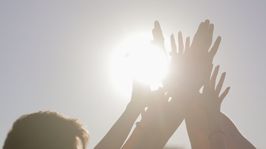 Close up, people raise their hands up to the sky and join their palms together in the bright summer sun. Strengthening team spirit by joining hands together.  Royalty-Free Stock Footage #1068028973