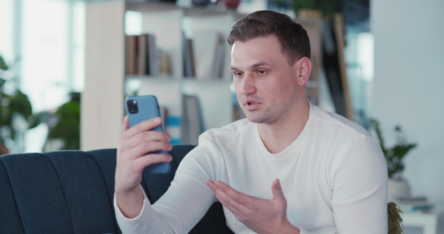 Young handsome adult man using mobile phone for webcam business talk video conference videochatting with corporate coworker at home. Royalty-Free Stock Footage #1068036911