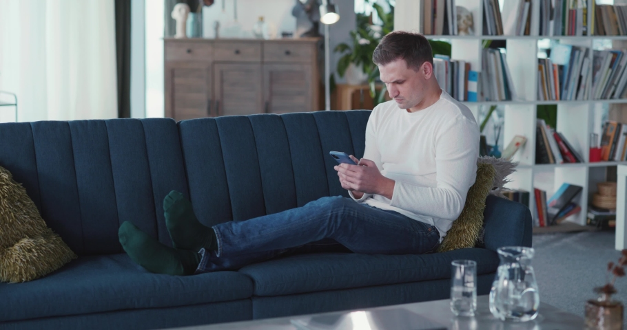 Young millennial businessman adult lying on couch using smartphone for connections surfing internet news staying home. Lifestyle. Modern people. Royalty-Free Stock Footage #1068036926