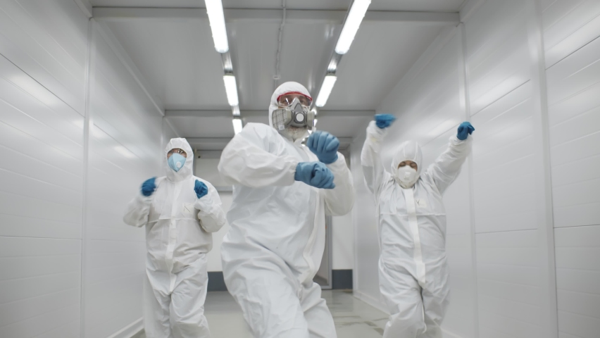 Team of medical workers in hazmat suits dancing and walking in hospital corridor. Funny disinfectors in respiratory mask and protective uniform dancing celebrating end of epidemic Royalty-Free Stock Footage #1068055358