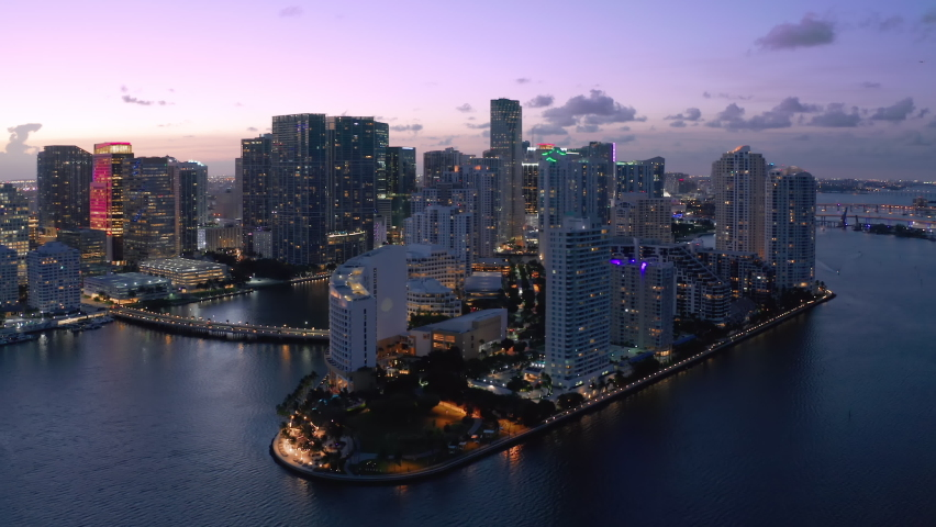 Modern architecture waterfront skyscraper glass buildings in foreground, Miami city in background. USA Florida sunset dusk purple colors of sky. Establishing aerial view shot of Miami downtown skyline
