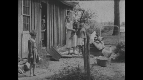1940s: Rural family sits on porch of house in mountain valley. Grandmother holds baby on lap and smiles. Families stand and sit near simple wooden homes in mountain valley.