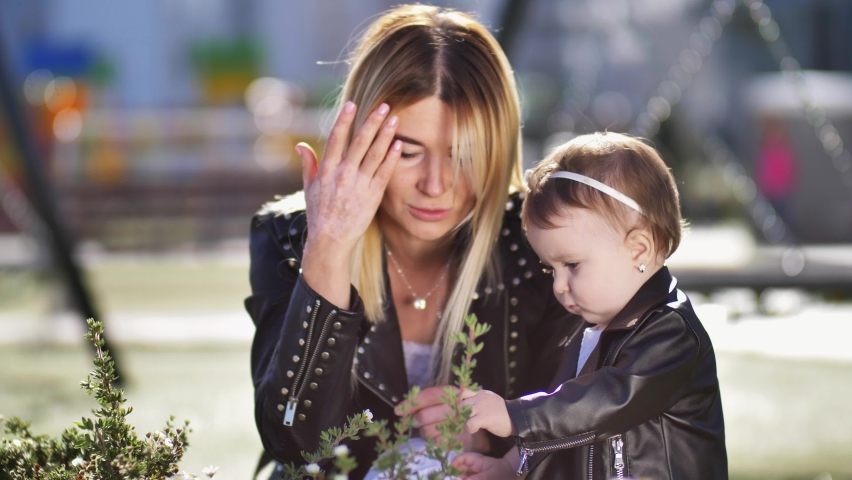 Attractive blonde woman communicating with little daughter while curious baby touching bush and trying to pick flower. Adorable one year old girl exploring the world together with loving mom | Shutterstock HD Video #1068069923