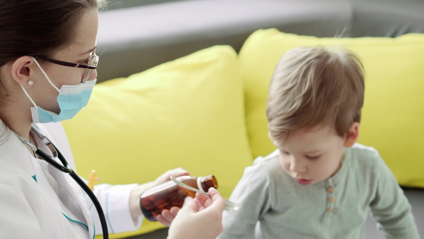 Close up of young woman nurse or doctor Caucasian Slavic ethnicity gives potion from spoon 3-4 years minor preschool boy kid on yellow gray sofa. medicine and health, pediatrics, covid-19 concept | Shutterstock HD Video #1068071198