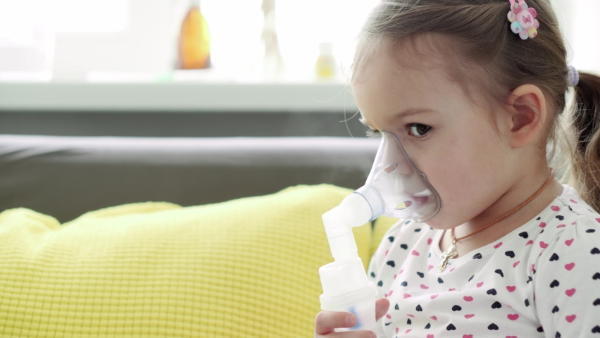 Close up Caucasian 3-4 years minor preschool girl kid in the mask of an inhaler on yellow gray sofa. Baby taking respiratory therapy with nebulizer. medicine and health, pediatrics, covid-19 concept | Shutterstock HD Video #1068071363