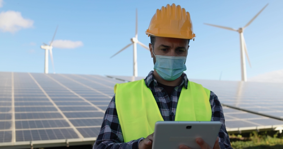 Young man working with digital tablet while wearing safety mask at wind farms - Renewable energy concept | Shutterstock HD Video #1068072467