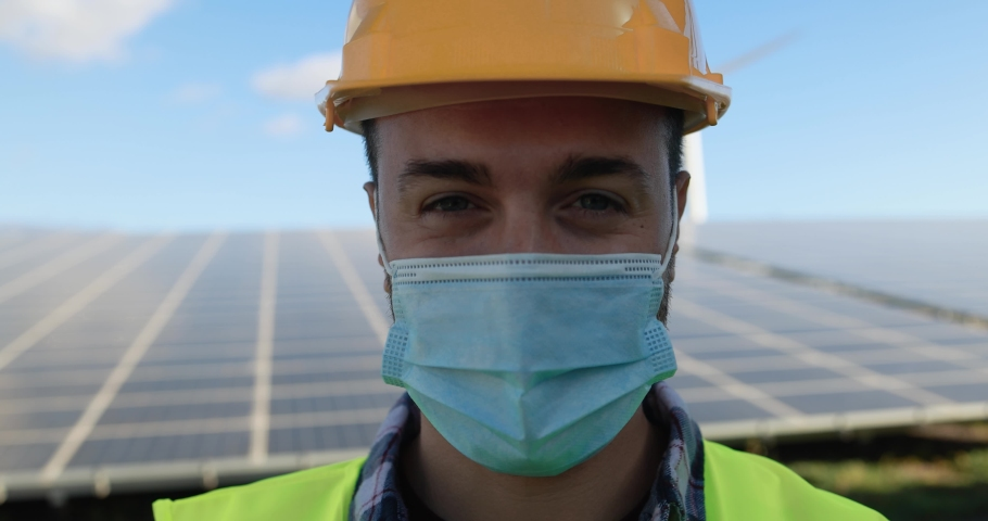 Young man working at solar power station while wearing safety face mask  | Shutterstock HD Video #1068072500