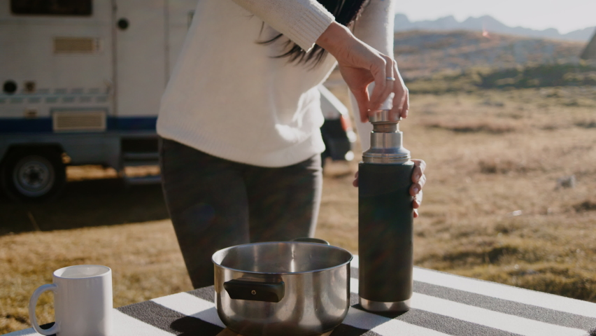 Woman using thermos and standing at table while traveling by camper car in countryside rbbro. Closeup view of young female traveler closes bottle cap and stands at desk outdoors on autumn day, man is | Shutterstock HD Video #1068105962