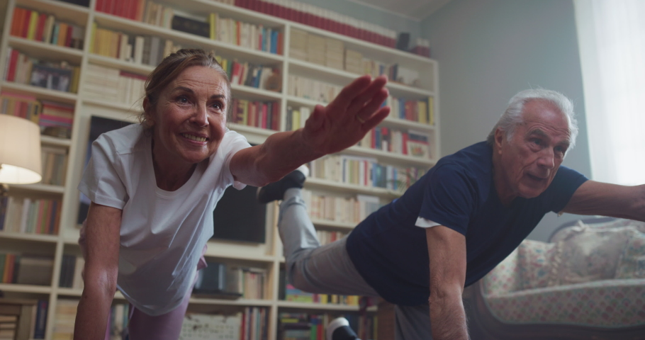 Cinematic shot of happy smiling mature senior couple doing exercises of gymnastics together at home. Concept of healthy lifestyle, fitness, recreation, couple goals, well being, retirement, elderly. Royalty-Free Stock Footage #1068106478