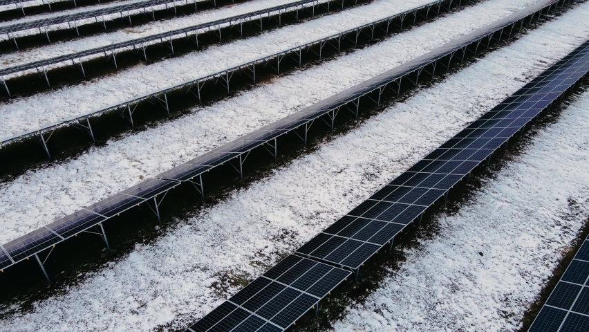 Amazing close up view of solar panels stand in rows in snowy fields for production green energy in winter landscape. Drone shoots video of concept of alternative power source | Shutterstock HD Video #1068117071