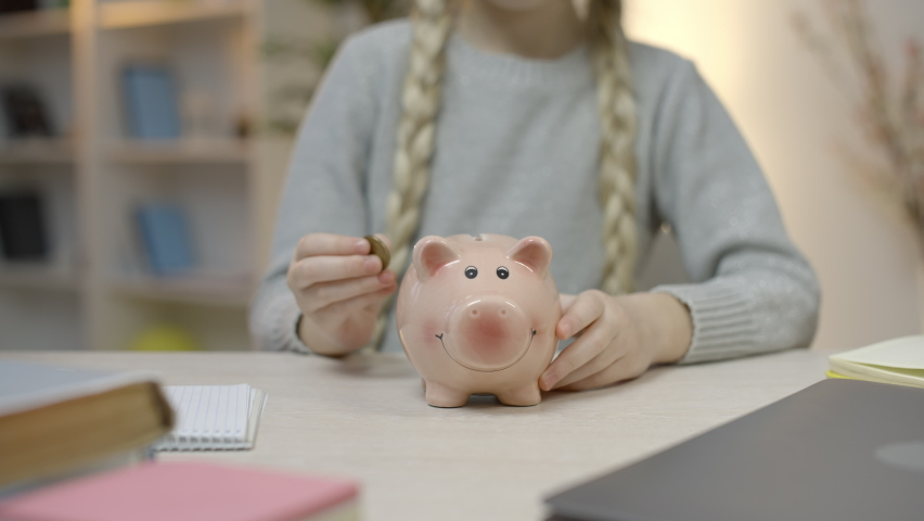 Little girl with braids putting coins in piggy bank, saving money, economy | Shutterstock HD Video #1068119180