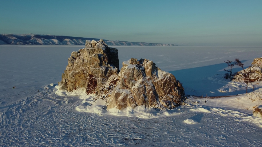 Baikal lake aerial flight around sacred Shaman rock at sunset in winter | Shutterstock HD Video #1068120605