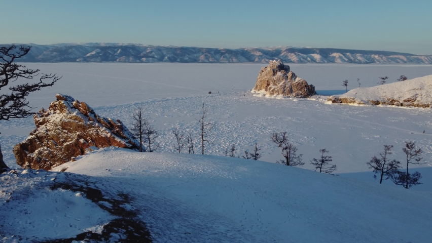 Baikal lake aerial flight near a lonely tree on the background of a sacred Shaman rock at sunset in winter | Shutterstock HD Video #1068120608