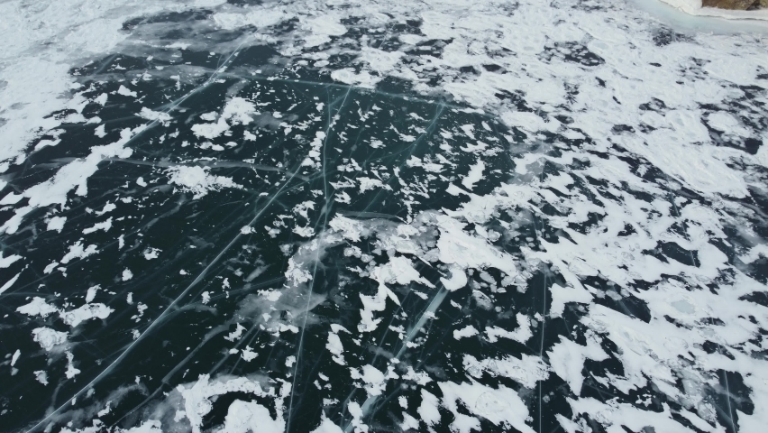 Baikal frozen lake, Olkhon island - Shaman rock, Burkhan cape aerial. Clear ice and snow. Travelling in winter at Russian Siberia | Shutterstock HD Video #1068120611