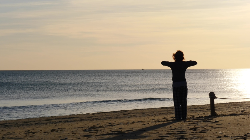 Woman in pajamas at morning time on beach. Female stretching, doing sports outdoors. Slow motion. Active living concept. Taking care of health. Reducing stress by exercising. | Shutterstock HD Video #1068120935