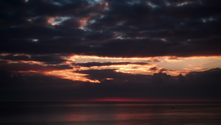 Seascape at early morning. Time lapse of dark stormy clouds moving over sea at sunrise. Nature landscape in Spain. | Shutterstock HD Video #1068121346