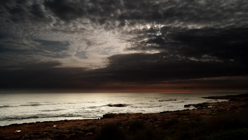 Seascape at morning. Dark clouds over sea with sunlight on horizon. | Shutterstock HD Video #1068121352