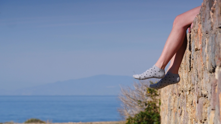 Vacation and carefree. Woman feet in dotted socks against blue sky and sea water. Female sitting on stone wall, dangling her legs, relaxing enjoying sun on sunny summer day. | Shutterstock HD Video #1068121361
