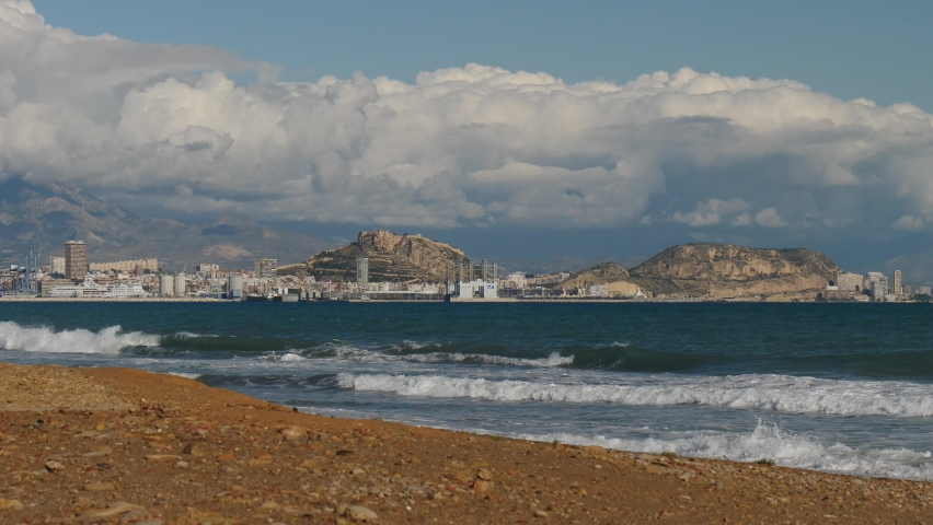 Alicante, Valencia, Spain - December 5, 2019: Mediterranean coast landscape with view from distance of Alacant city and Castle of Santa Barbara on Mount Benacantil. Spain, Costa Blanca. Sea waves in s | Shutterstock HD Video #1068121385