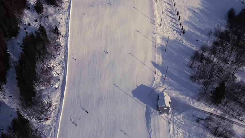 Top down view of skiers riding down a steep slope at a winter sports resort. | Shutterstock HD Video #1068121679