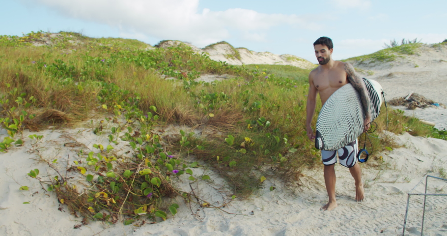 Man walks on the beach with surfboard and holds it in the sand while preparing to surf | Shutterstock HD Video #1068122387