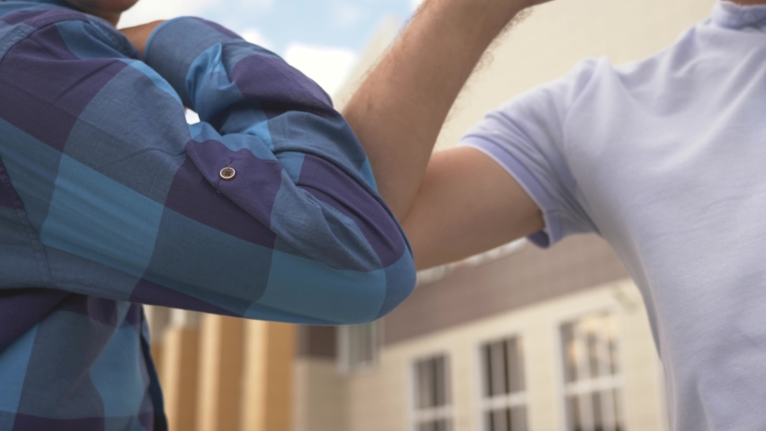 Elbow greetings on street. Social distance. Prevention of coronavirus infection. Two business man greet with elbows from distance. Coronavirus safety. Social distance elbow greetings. Two business man Royalty-Free Stock Footage #1068132938