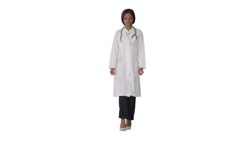 Sad African american female doctor walking with hands in her pockets on white background.